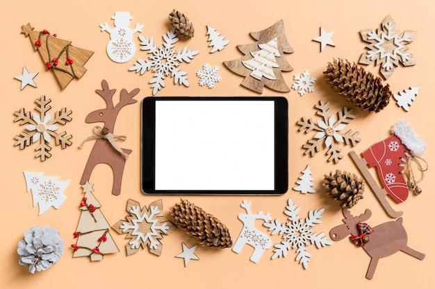 Draufsicht der digitalen tablette umgeben mit spielwaren und dekorationen des neuen jahres auf orange.