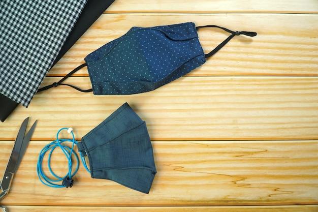 Draufsicht der diy dunkelblauen stoffgesichtsmaske auf holztisch. schützen sie speichel, husten, staub, verschmutzung (pm2.5), viren, bakterien, coronaviren (covid-19). handgemachtes konzept. speicherplatz kopieren.