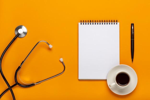 Draufsicht der doktorschreibtischtabelle mit stethoskop, kaffee und leerem papier auf klemmbrett mit stift. draufsicht mit kopienraum, flach legen