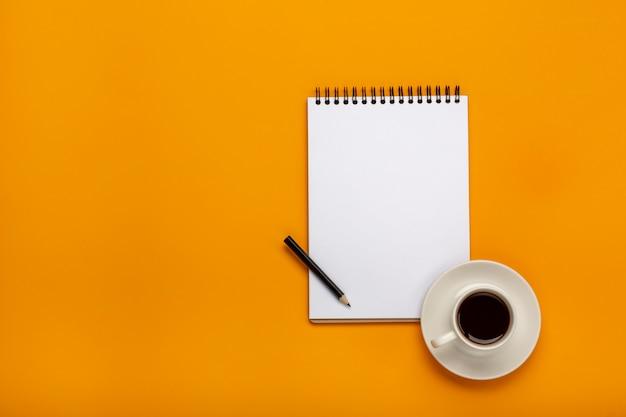 Draufsicht der doktorschreibtischtabelle mit stethoskop, kaffee und leerem papier auf klemmbrett mit stift