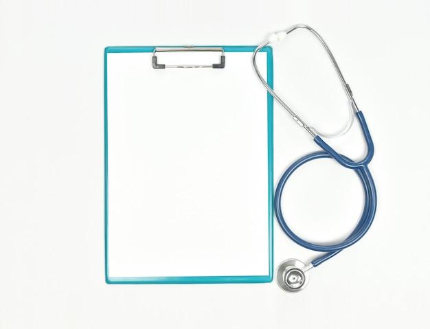 Draufsicht der doktorschreibtischtabelle mit stethoskop und leerem papier auf klemmbrett.