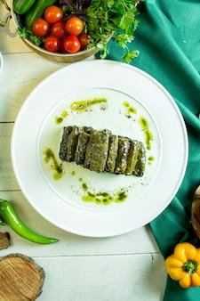 Draufsicht der dolma der traditionellen kaukasischen küche mit weinblättern auf einem teller
