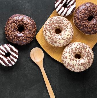 Draufsicht der donuts auf schneidebrett mit holzlöffel
