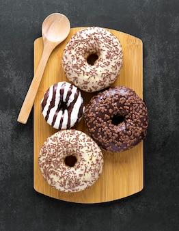 Draufsicht der donuts auf schneidebrett mit löffel
