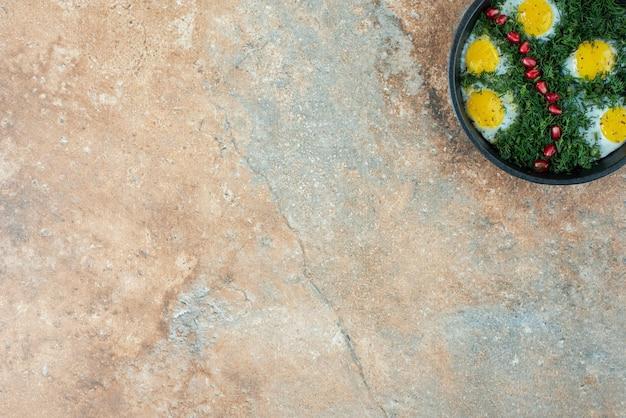 Draufsicht der dunklen pfanne mit omelett und grüns.