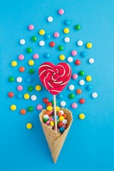 Draufsicht der eistüte mit herzförmigen süßigkeiten und bunten süßigkeiten auf dem blau