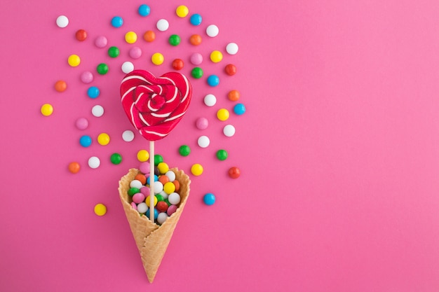 Draufsicht der eistüte mit herzförmigen süßigkeiten und bunten süßigkeiten
