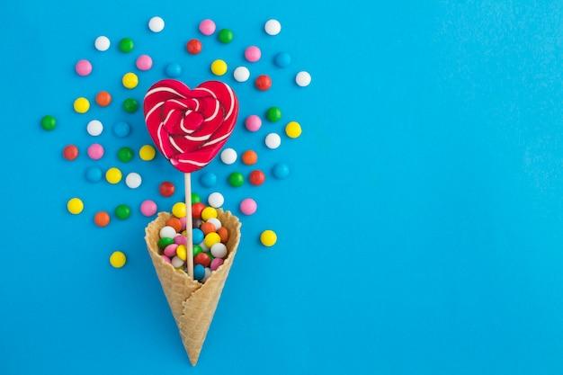 Draufsicht der eistüte mit herzförmiger süßigkeit und bunter süßigkeit auf blau