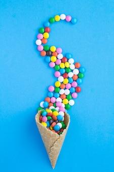Draufsicht der eistüte mit süßigkeit auf dem blau