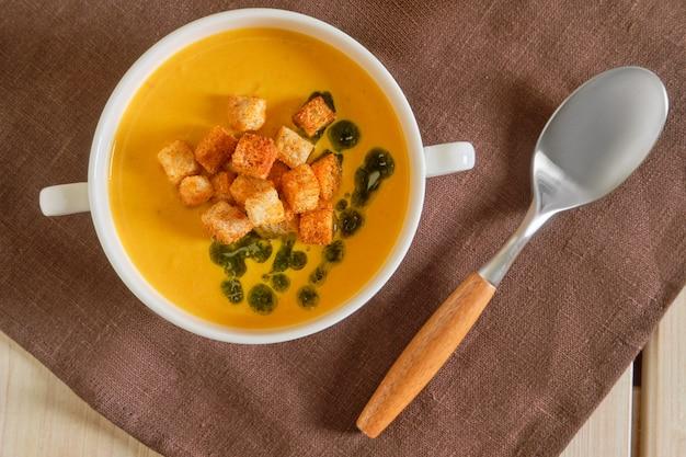 Draufsicht der erbsensuppe mit curry und crouton auf holztisch