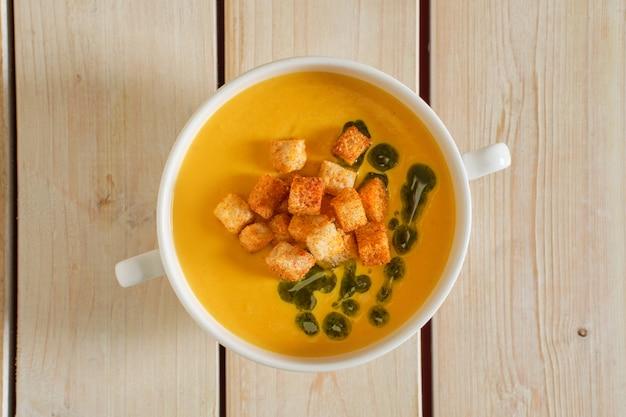 Draufsicht der erbsensuppe mit curry und crouton