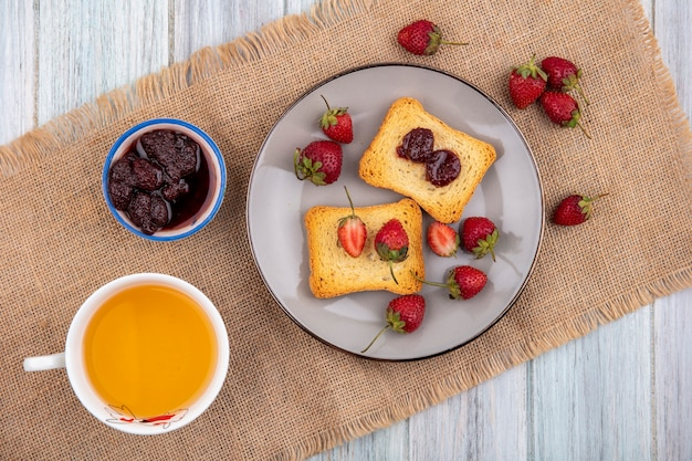 Draufsicht der erdbeere auf einem teller auf einem sackstoff mit einer tasse tee mit erdbeermarmelade auf einem grauen hölzernen hintergrund