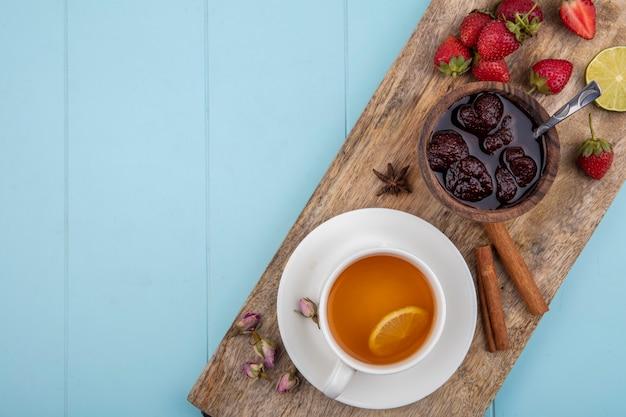 Draufsicht der erdbeermarmelade auf einem hölzernen küchenbrett mit einer tasse tee mit zimtstangen auf einem blauen hintergrund mit kopienraum
