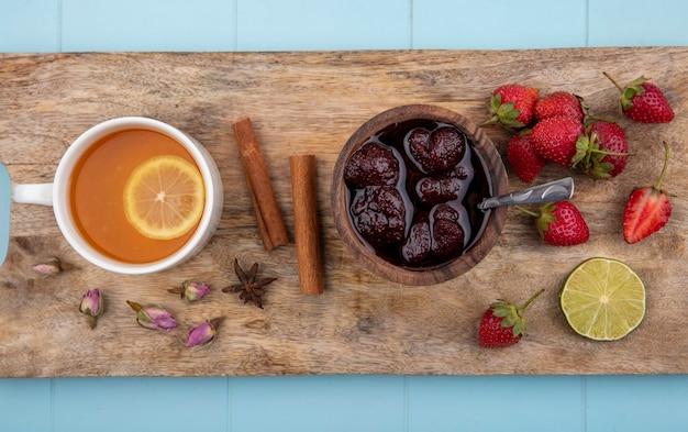 Draufsicht der erdbeermarmelade auf einem hölzernen küchenbrett mit einer tasse tee mit zimtstangen auf einem blauen hintergrund
