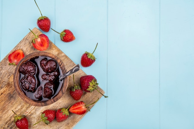 Draufsicht der erdbeermarmelade auf einer hölzernen schüssel mit frischen erdbeeren auf einem weißen hintergrund mit kopienraum