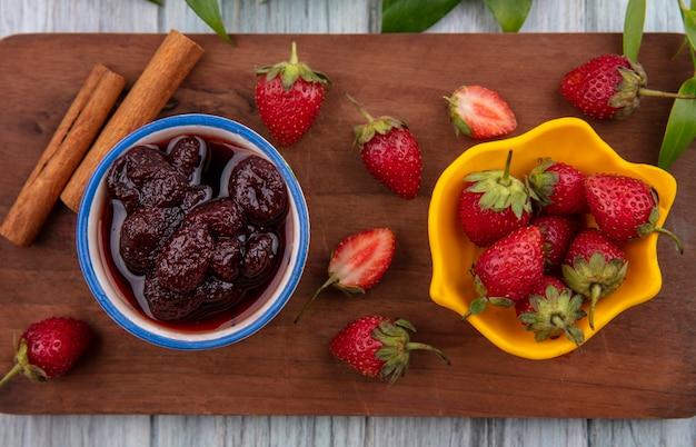 Draufsicht der erdbeermarmelade auf einer schüssel auf einem hölzernen küchenbrett mit frischen erdbeeren auf einer gelben schüssel mit zimtstangen auf einem grauen hölzernen hintergrund
