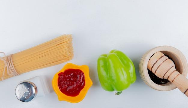 Draufsicht der fadennudelmakkaroni mit ketchuppfeffer des schwarzen pfeffers auf weiß