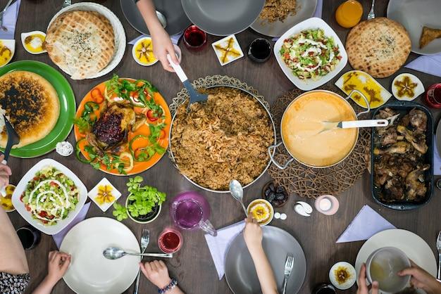 Draufsicht der familie und der freunde, die lebensmittel auf tabelle essen