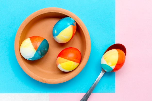 Draufsicht der farbigen eier für ostern auf teller mit löffel