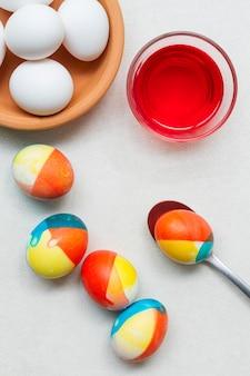 Draufsicht der farbigen eier mit farbe und löffel für ostern