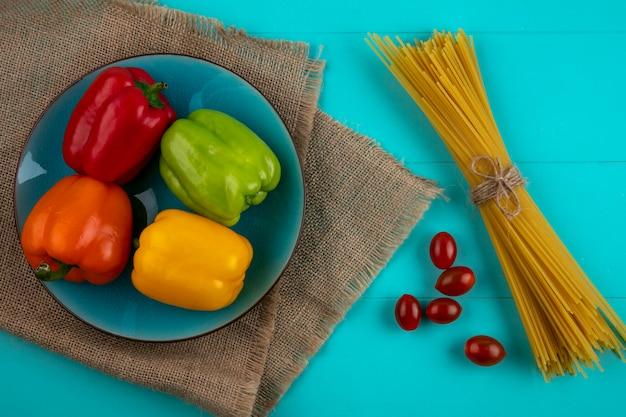 Draufsicht der farbigen paprika auf einem blauen teller mit rohen nudeln und kirschtomaten auf einer türkisfarbenen oberfläche