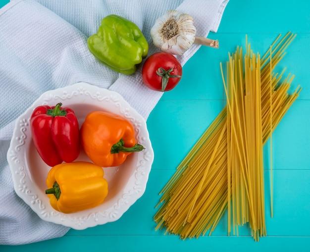 Draufsicht der farbigen paprika in einem weißen teller auf einem weißen handtuch mit rohen spaghettitomaten und knoblauch