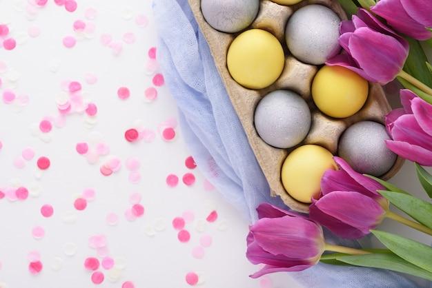 Draufsicht der festlichen osterkomposition der purpurnen tulpen und der gelben und blauen ostereier mit rosa konfetti auf weißem hintergrund