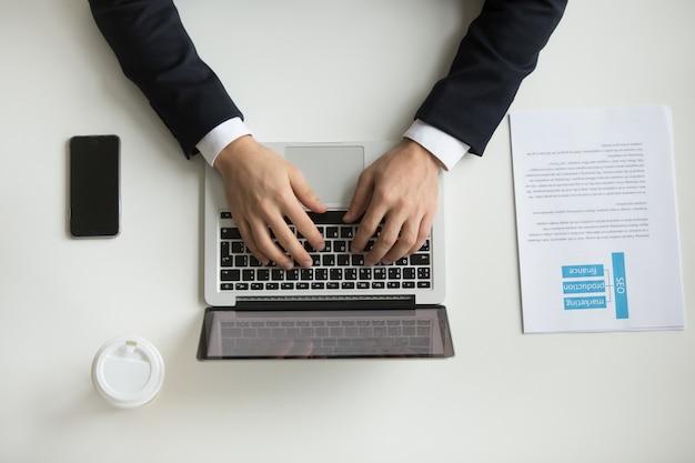 Draufsicht der firma ceo, die am laptop schreibt