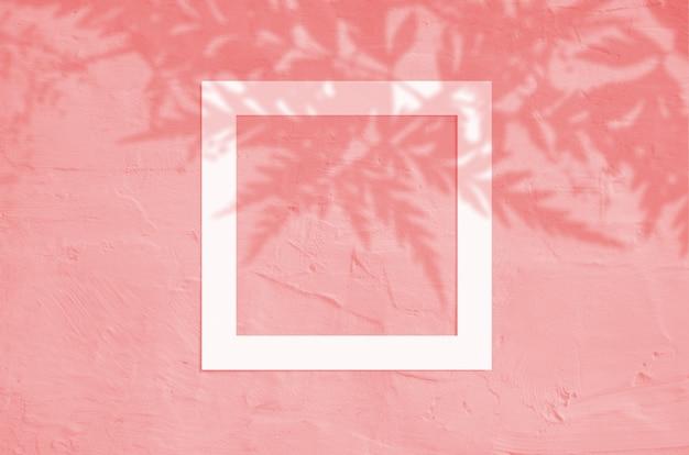 Draufsicht der flachen lage kreativen copyspace mit papierrahmen und tropischem blattpalmenschatten auf korallenroter farbe.
