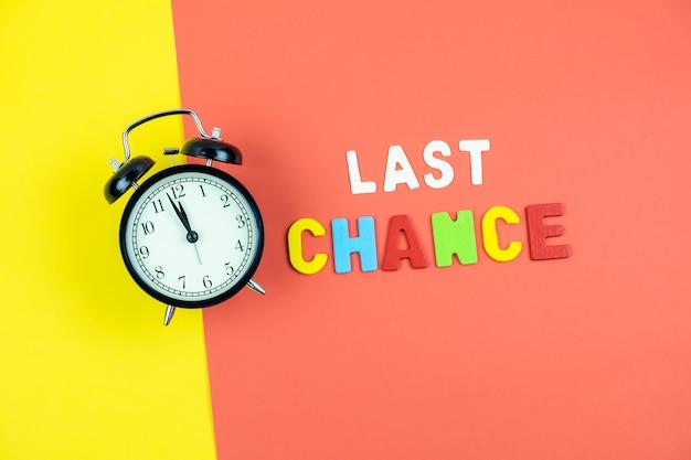Draufsicht der formulierung der letzten chance und des weckers auf buntem tisch