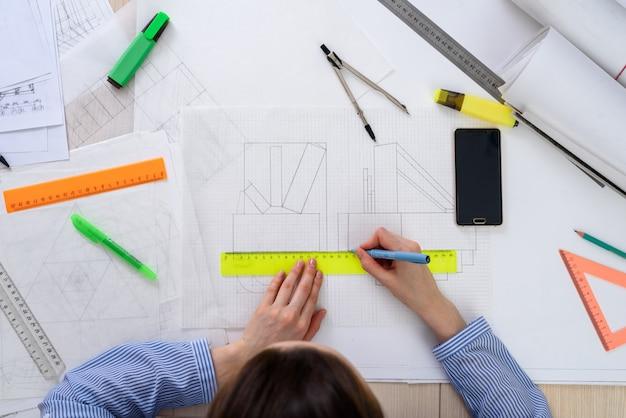 Draufsicht der frau des architekten bei der arbeit über das design des gebäudes, auf dem tisch papier, machthaber, bleistifte, kompass, smartphone, verdrehte zeichnung.