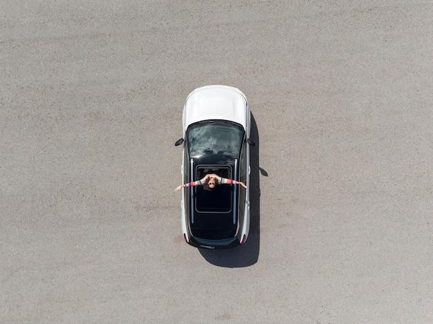Draufsicht der frau, die aus dem autofenster steht