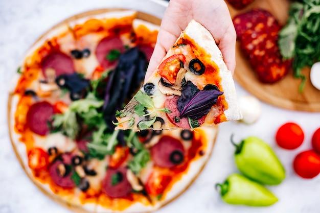 Draufsicht der frau, die ein stück peperoni-pizza mit oliventomatenpilz und kräutern hält