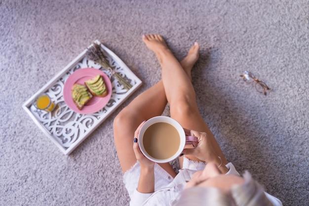 Draufsicht der frau, die eine heiße tasse kaffee in den pyjama-kleidern hält