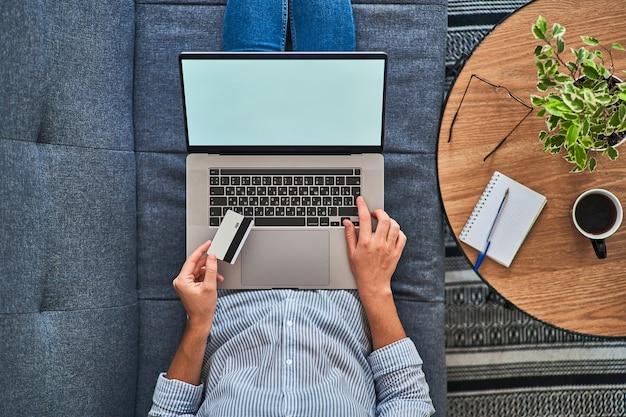 Draufsicht der frau, die eine kreditkarte hält und online an einem computer einkauft.