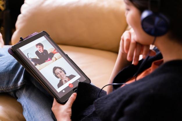 Draufsicht der frau, die einen freund mit tablet-gerät anruft. soziales distanzkonzept in quarantäneisolation zu hause. technologielebensstil im haus.