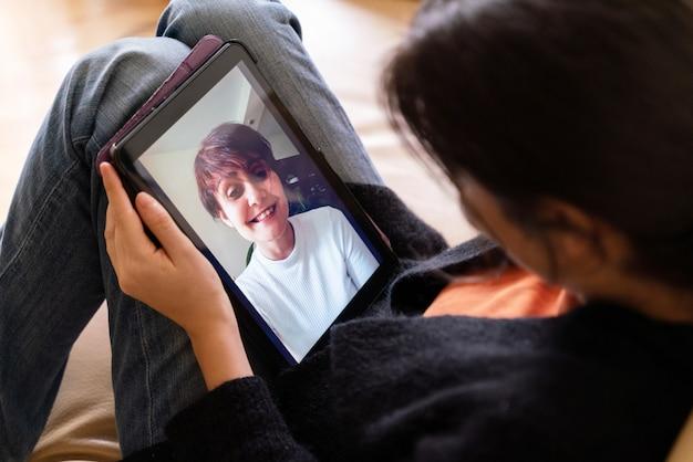 Draufsicht der frau, die einen freund mit technologiegerät für video-chat und gespräch anruft. bleiben sie zu hause und soziale distanz konzept.