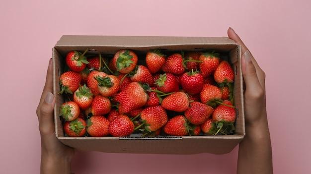 Draufsicht der frau, die kasten mit frischer erdbeere hält