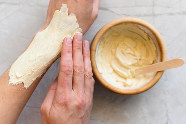 Draufsicht der frau, die lotion auf ihren händen aufträgt
