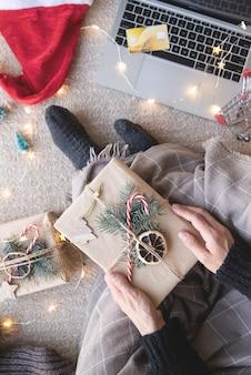 Draufsicht der frau, die online an den weihnachtsferien einkauft, die die geschenkbox halten