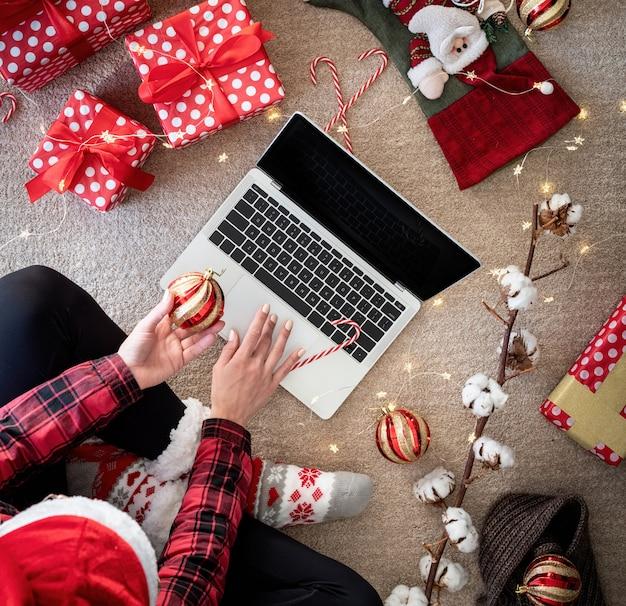 Draufsicht der frau, die online an den weihnachtsferien einkauft, die geschenkbox halten