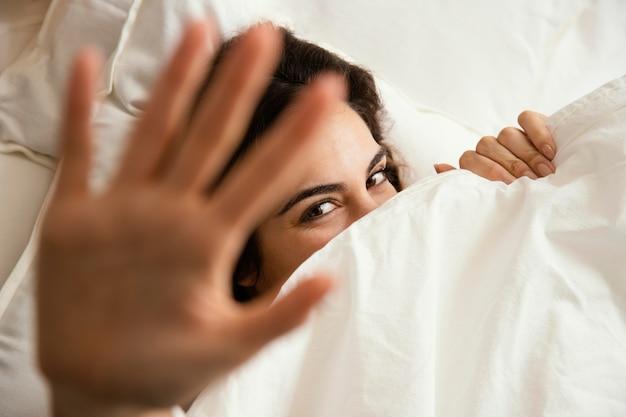 Draufsicht der frau, die sich zu hause unter den laken versteckt