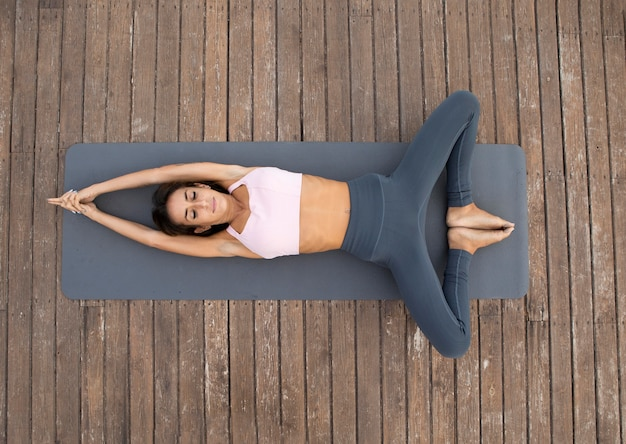 Draufsicht der frau, die yoga im freien tut