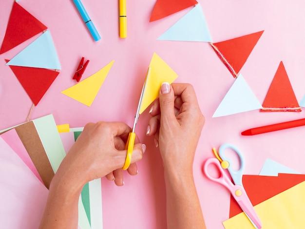 Draufsicht der frau farbiges papier schneiden