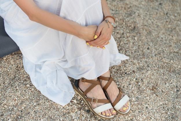 Draufsicht der frau im langen weißen kleid, das auf sandstrand sitzt und ihre knie umarmt.