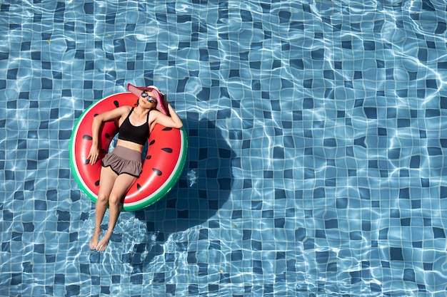 Draufsicht der frau lag auf ballon im pool