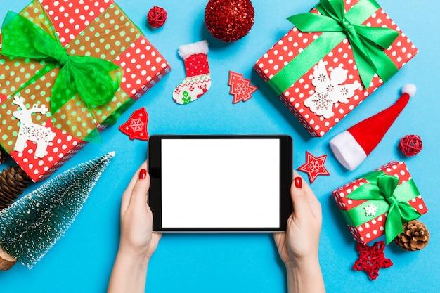 Draufsicht der frau tablette in ihren händen auf dem blauen hintergrund halten gemacht von den weihnachtsdekorationen. neujahrsfeiertagskonzept. attrappe, lehrmodell, simulation