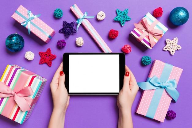 Draufsicht der frau tablette in ihren händen auf dem purpur halten gemacht von den weihnachtsdekorationen.