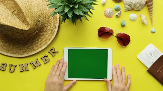 Draufsicht der frauenhände, die digitales tablett mit grünem bildschirm, sommerzubehör halten. sommerferienstrandhintergrund, reisesommerkonzept