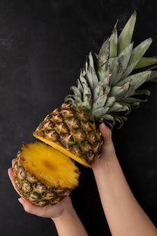 Draufsicht der frauenhände, die geschnittene ananas auf schwarzer oberfläche halten